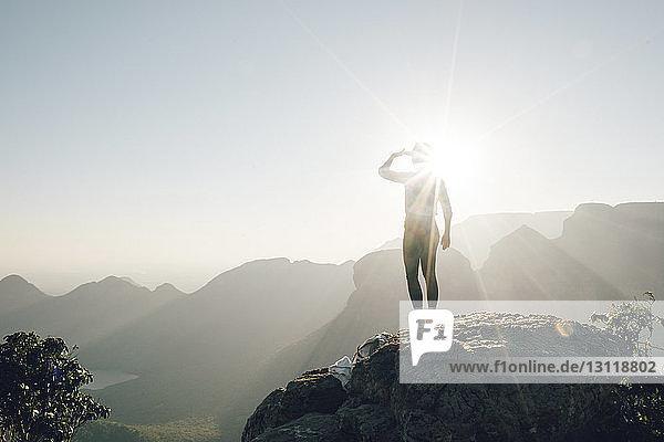 Rückansicht einer Frau  die auf Berge schaut  während sie am sonnigen Tag auf einem Felsen gegen den Himmel steht