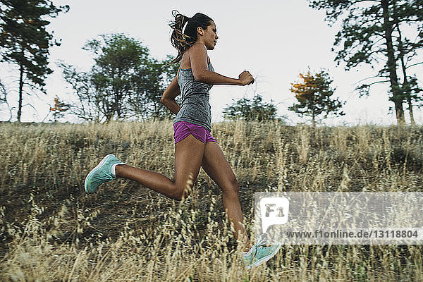 Low angle view of sportswoman running on grassy field
