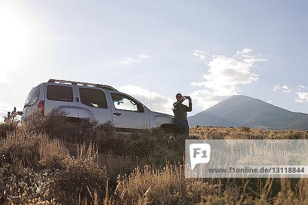 Mann fotografiert  während er im Auto auf dem Feld steht