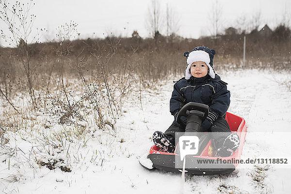 Full length portrait of cute baby boy sitting on sled amidst snow
