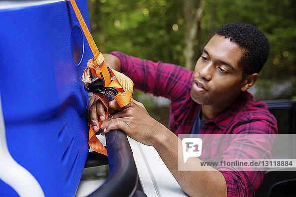 Young man tying cooler on roofrack of car during vacation