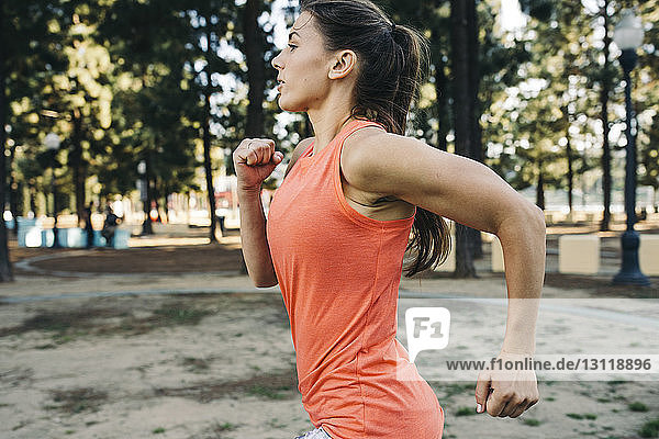 Side view of determined athlete running at park