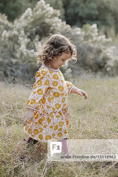 Side view of girl walking on grassy field