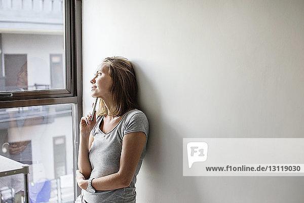 Nachdenkliche Frau  die durch ein Fenster schaut  während sie sich zu Hause an eine weiße Wand lehnt