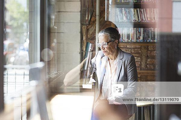 Seriöse reife Frau sitzt am Tisch,  gesehen durch Glas im Café