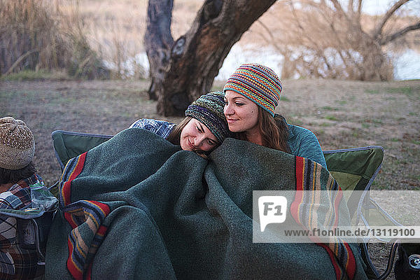 Liebevolle Freundinnen mit Decke zugedeckt auf dem Zeltplatz sitzend