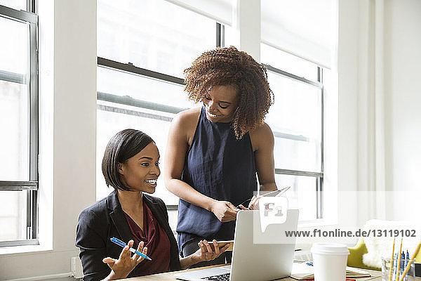 Fröhliche Geschäftsfrauen diskutieren im kreativen Büro