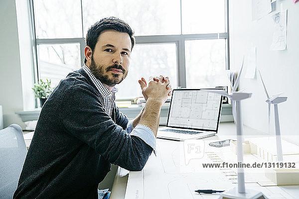 Porträt eines Geschäftsmannes mit gefalteten Händen am Schreibtisch sitzend im Büro