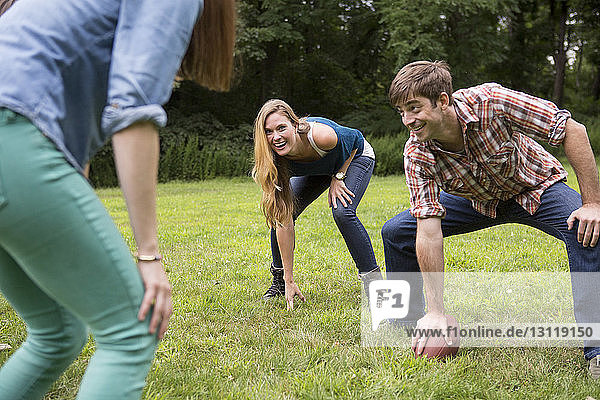 Mann hält Fussball in der Hand  während er Freundinnen auf dem Rasenplatz ansieht