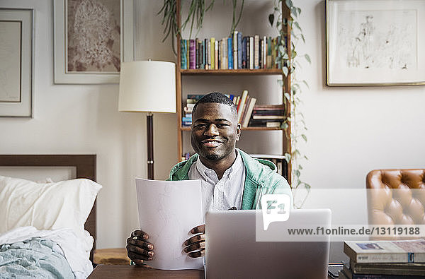 Portrait of happy man holding documents while working at home