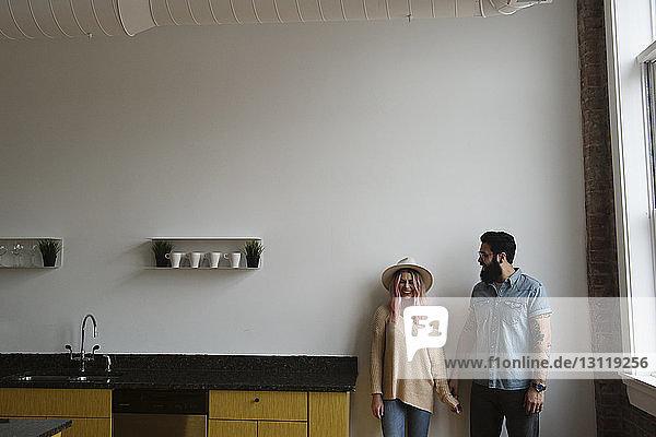 Glückliches Paar  das zu Hause in der Küche an der Wand steht