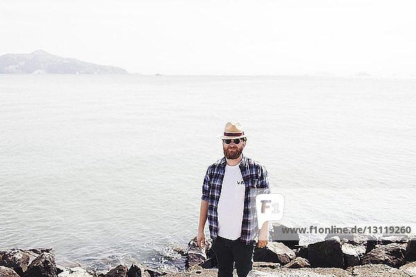 Porträt eines Mannes mit Hut und Sonnenbrille  der gegen das Meer steht