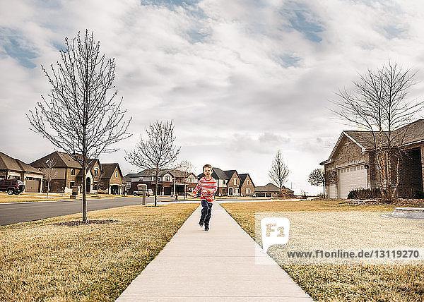 Boy running on sidewalk against sky