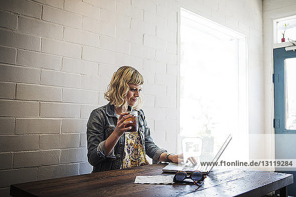 Woman using laptop while holding iced tea glass in cafe
