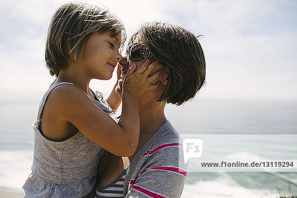 Close-up of mother carrying daughter while standing at beach