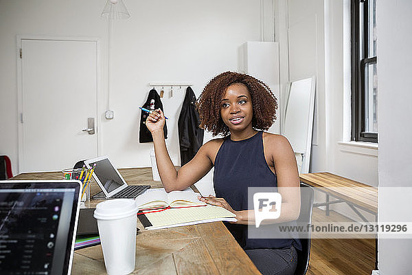 Zuversichtliche Geschäftsfrau schaut  während sie im Kreativbüro am Schreibtisch sitzt