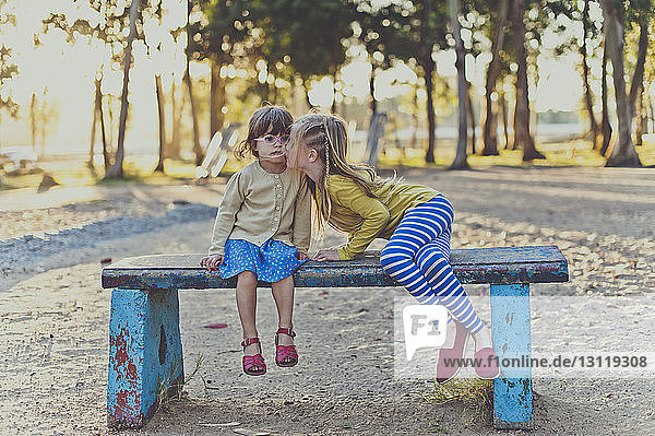Girl kissing sister while sitting on bench at park