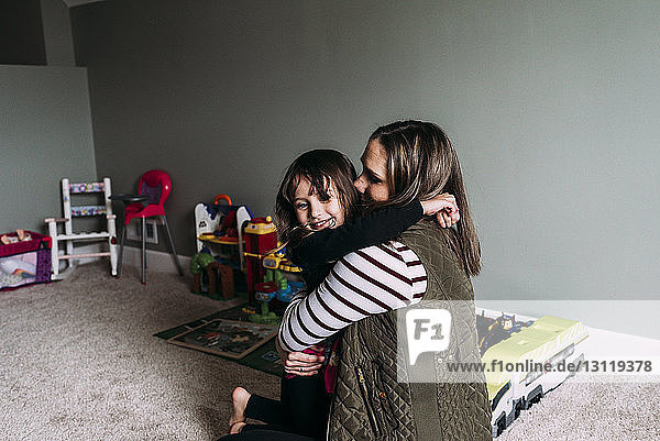Side view of happy mother embracing daughter at home