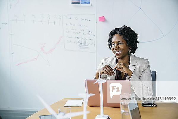Lächelnde Geschäftsfrau schaut weg  während sie mit Laptop-Computer im Sitzungssaal sitzt