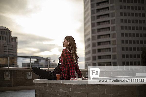 Junge Frau sitzt auf einem Sitzplatz auf einer Terrasse vor Gebäuden