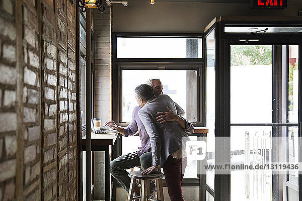 Couple embracing while sitting against windows at cafe