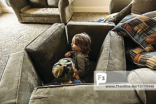 Verspielte Jungen  die sich zu Hause hinter Kissen verstecken
