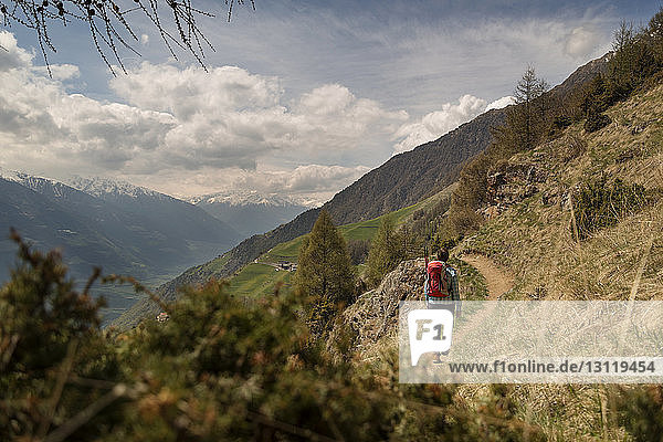Rear view of female hiker walking on mountain against cloudy sky