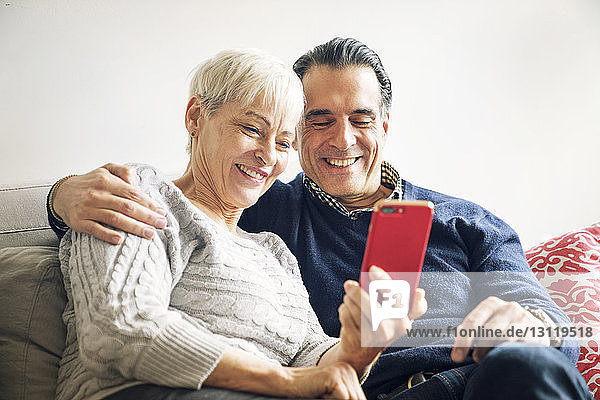 Smiling senior couple looking at smart phone while sitting on sofa at home