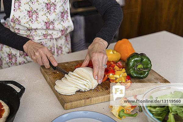 Mitschnitt einer Frau beim Käseschneiden während der Zubereitung von Speisen in der heimischen Küche