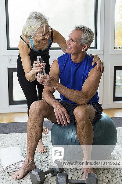 Frau verschenkt Wasserflasche an Mann  der zu Hause auf Fitnessball sitzt