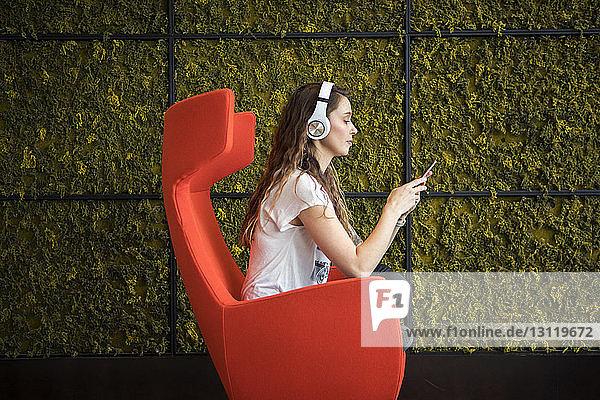 Seitenansicht einer Frau  die ein Smartphone benutzt  während sie zu Hause auf einem Sessel sitzt