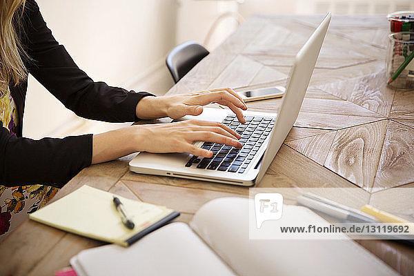 Beschnittenes Bild einer Geschäftsfrau mit Laptop am Schreibtisch im Büro