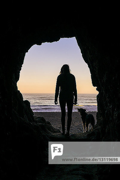 Silhouette woman with dog standing at cave entrance against beach