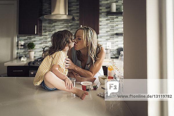Mutter küsst Tochter  die zu Hause auf dem Küchentisch sitzt