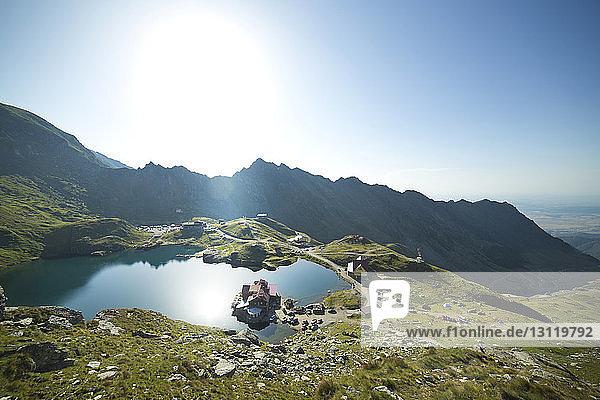 Hochwinkelansicht des Sees durch Berge gegen klaren Himmel