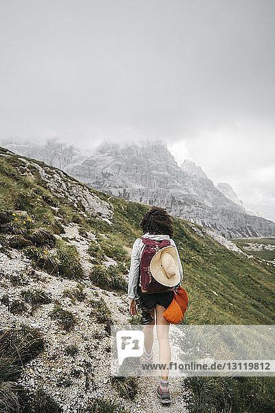 Rückansicht einer Wanderin  die auf einem Berg vor bewölktem Himmel wandert