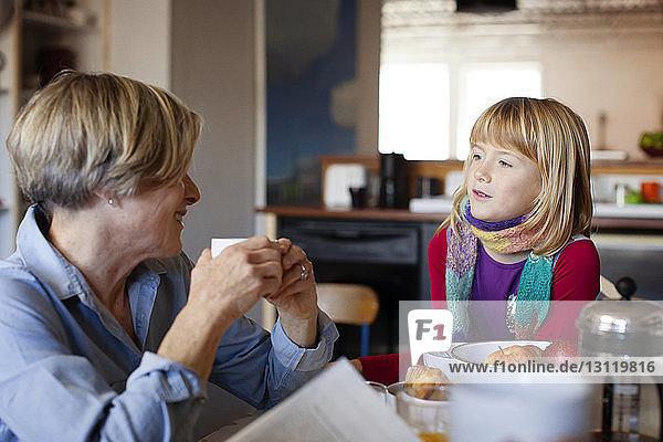 Großmutter und Enkelin unterhalten sich am Tisch