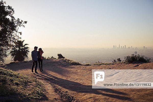 Paar zu Fuß auf der Straße am Berg gegen den Himmel