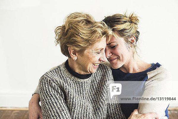 Nahaufnahme einer lächelnden Mutter und Tochter  die zu Hause an der Wand sitzen