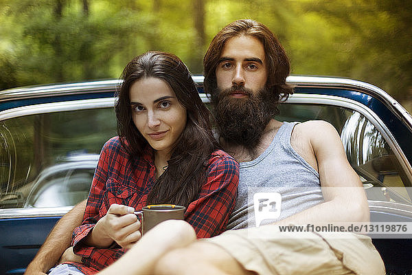 Portrait of confident couple sitting in pick-up truck in forest
