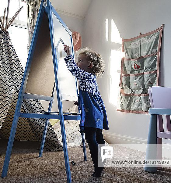 Seitenansicht eines Mädchens  das zu Hause auf Leinwand malt