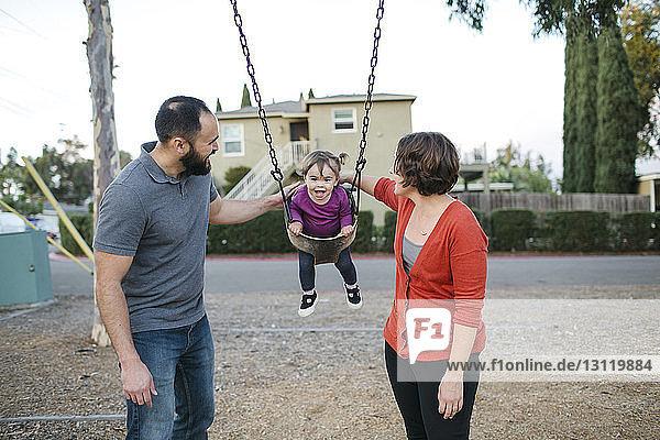 Vater und Mutter schaukeln ihre Tochter auf dem Spielplatz