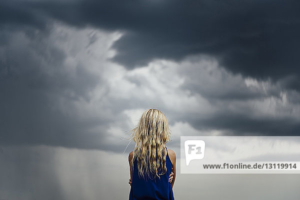 Rear view of girl standing against cloudy sky