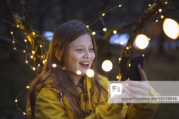 Cheerful girl using smart phone amidst illuminated string lights decoration at night