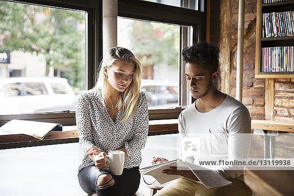 Mann zeigt Frau Papiere  während er im Café sitzt