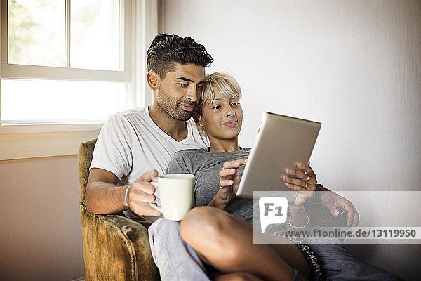 Junges Paar benutzt Tablet-Computer  während es zu Hause auf einem Sessel sitzt