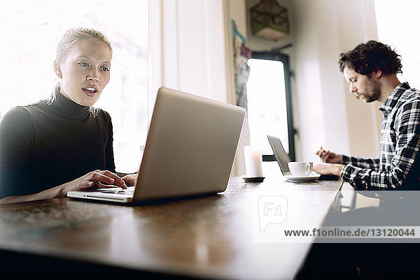 Man and woman using laptop in cafe