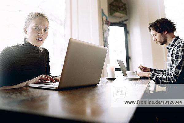 Mann und Frau mit Laptop im Café