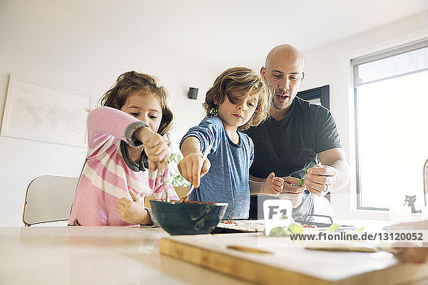 Father assisting son and daughter in preparing food at home