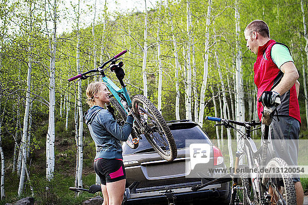 Side view of woman lifting bicycle while standing by man in forest